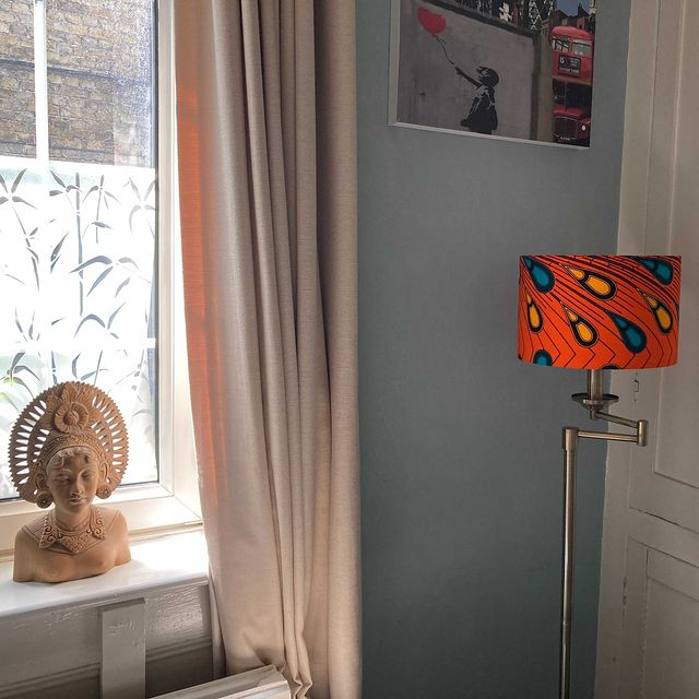 Orange African lampshade with peacock feathers handmde by Detola and Geek situated in a repeat customers home. Image credit @regalfbv (on instagram)