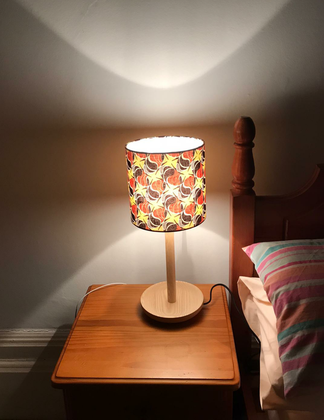 Small bedside table patterned with mixed brown & yellow seeds on an African print fabric. The light is switched on too