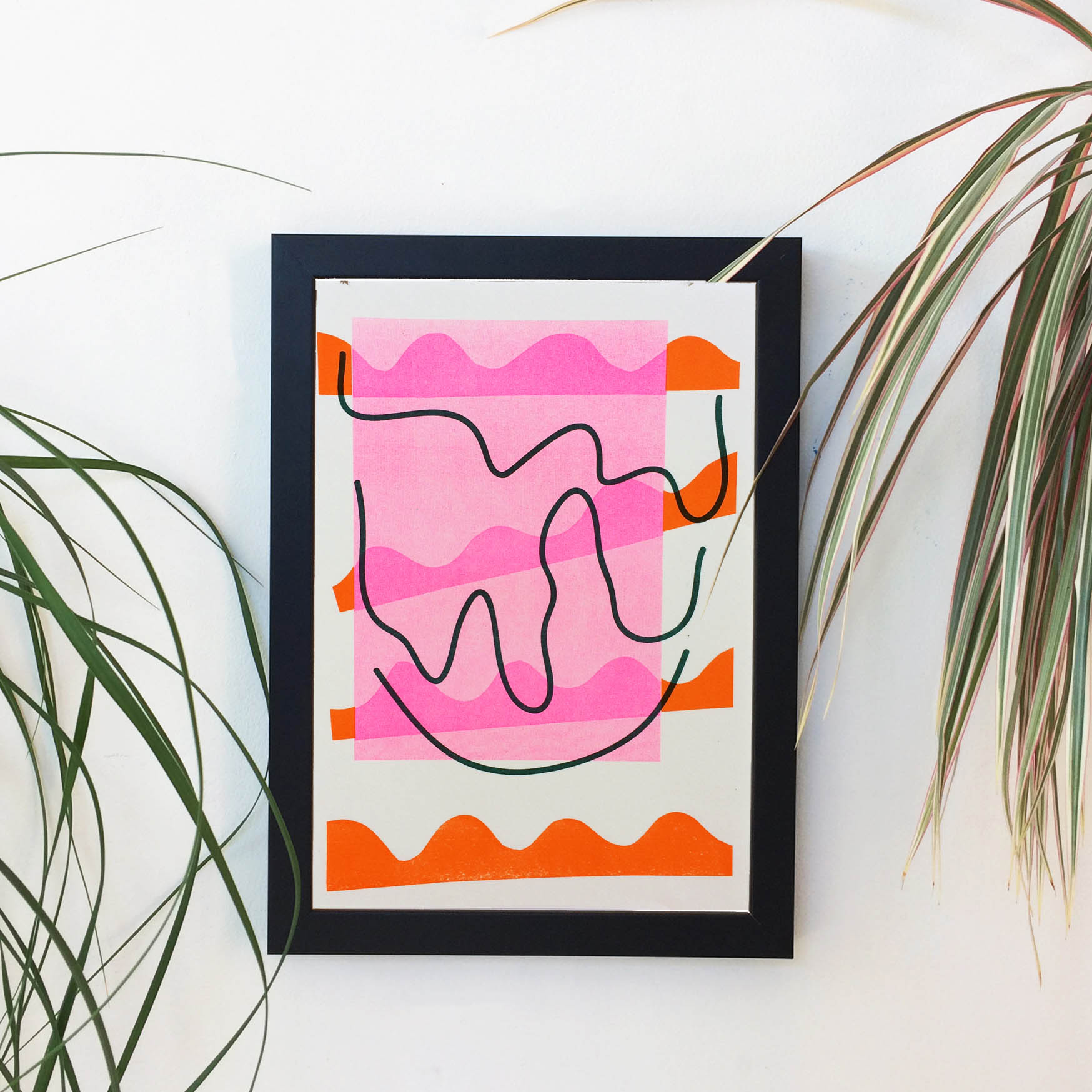 An abstract wiggly print in a frame in orange pink and teal