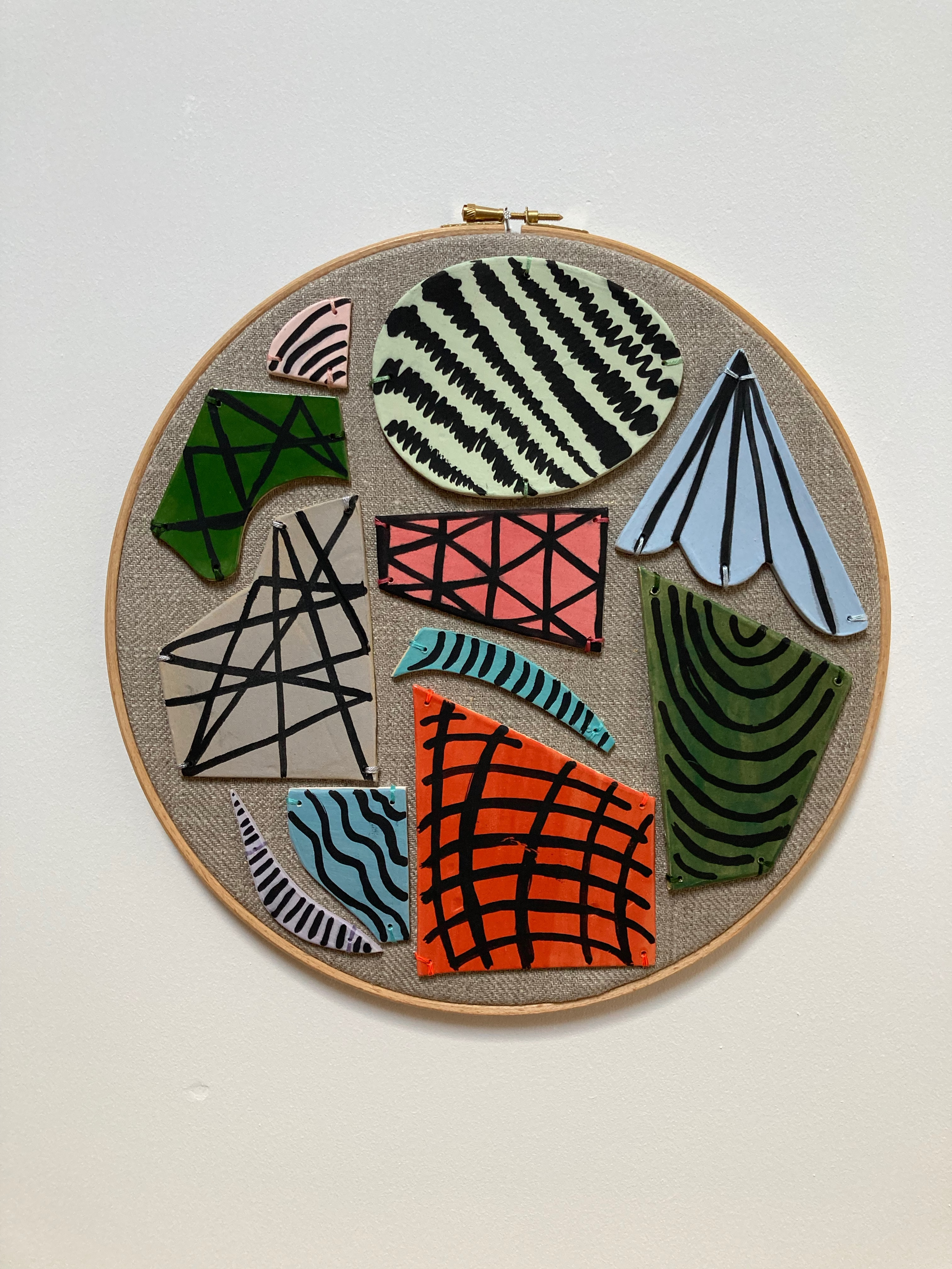 an embroidered hoop with pastel coloured ceramic shapes that have black ink painted marks and patterns