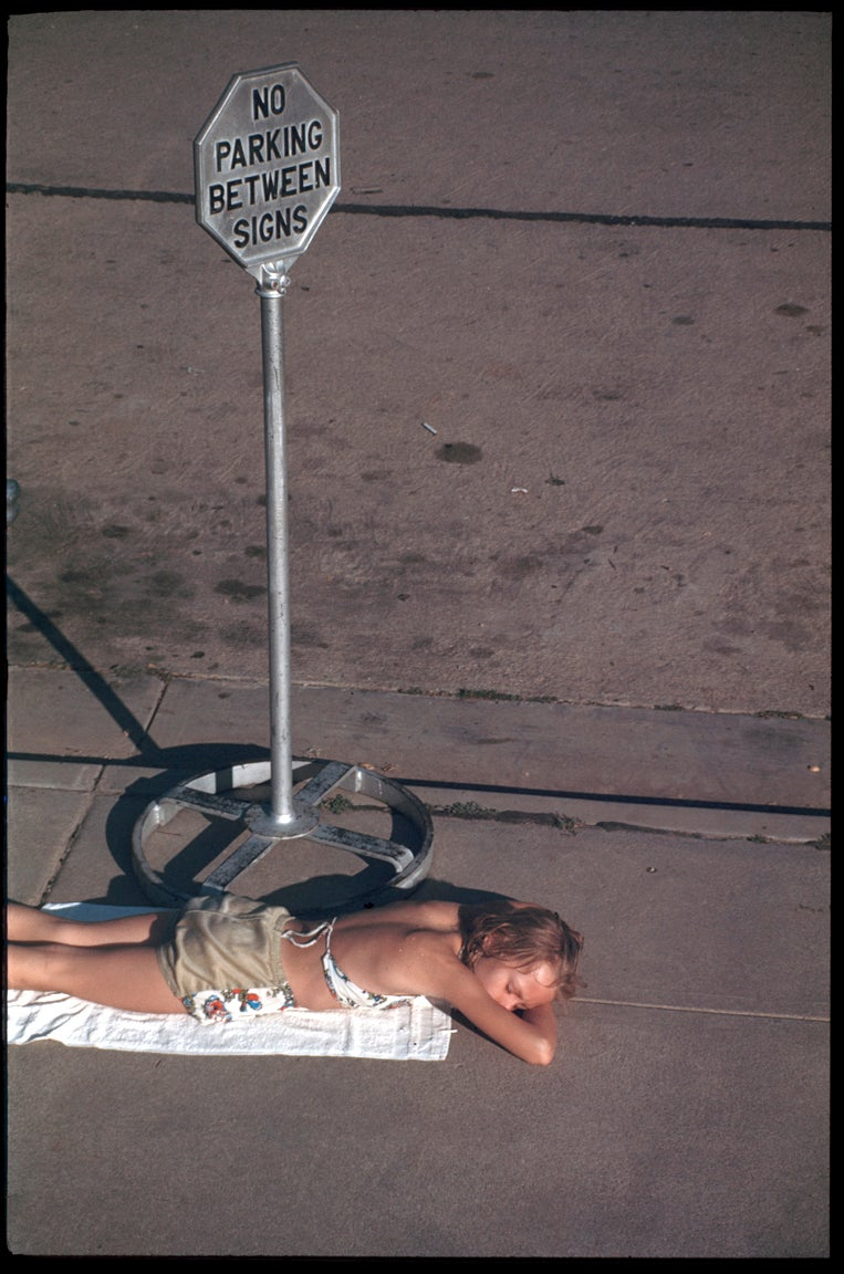Image of A Young Girl Sunbathes On The Sidewalk: 1960's