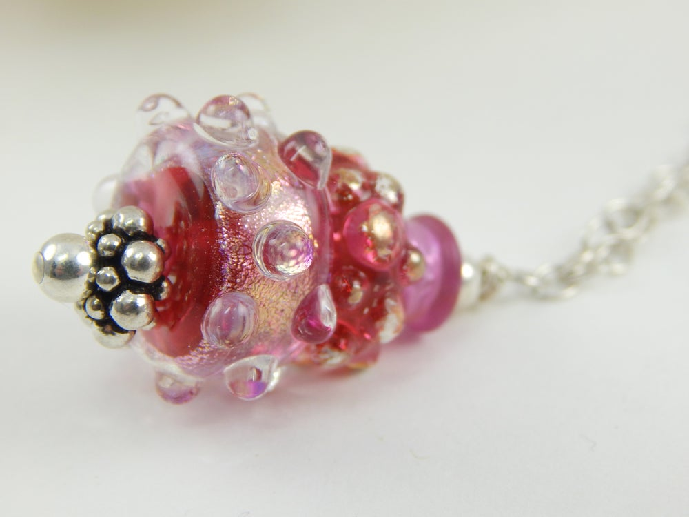 Image of Necklace. Pendant with lamp work glass in shades of pink.