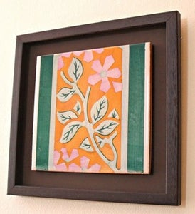 Image of Orange and lavander ceramic framed tile.