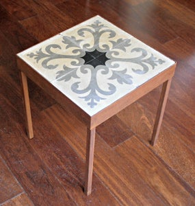 Image of Black fleur-de-lis end cement tile table