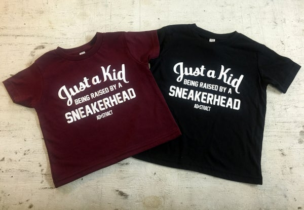 "Image of JUST A KID BEING RAISED BY A SNEAKERHEAD TSHIRT ""BLACK/MAROON"" (TODDLER)"