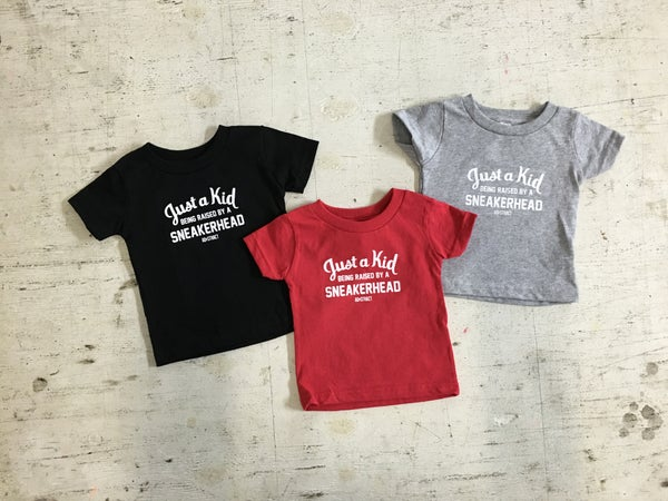 "Image of JUST A KID BEING RAISED BY A SNEAKERHEAD ""BLACK/RED/GREY"" TSHIRT (INFANT)"