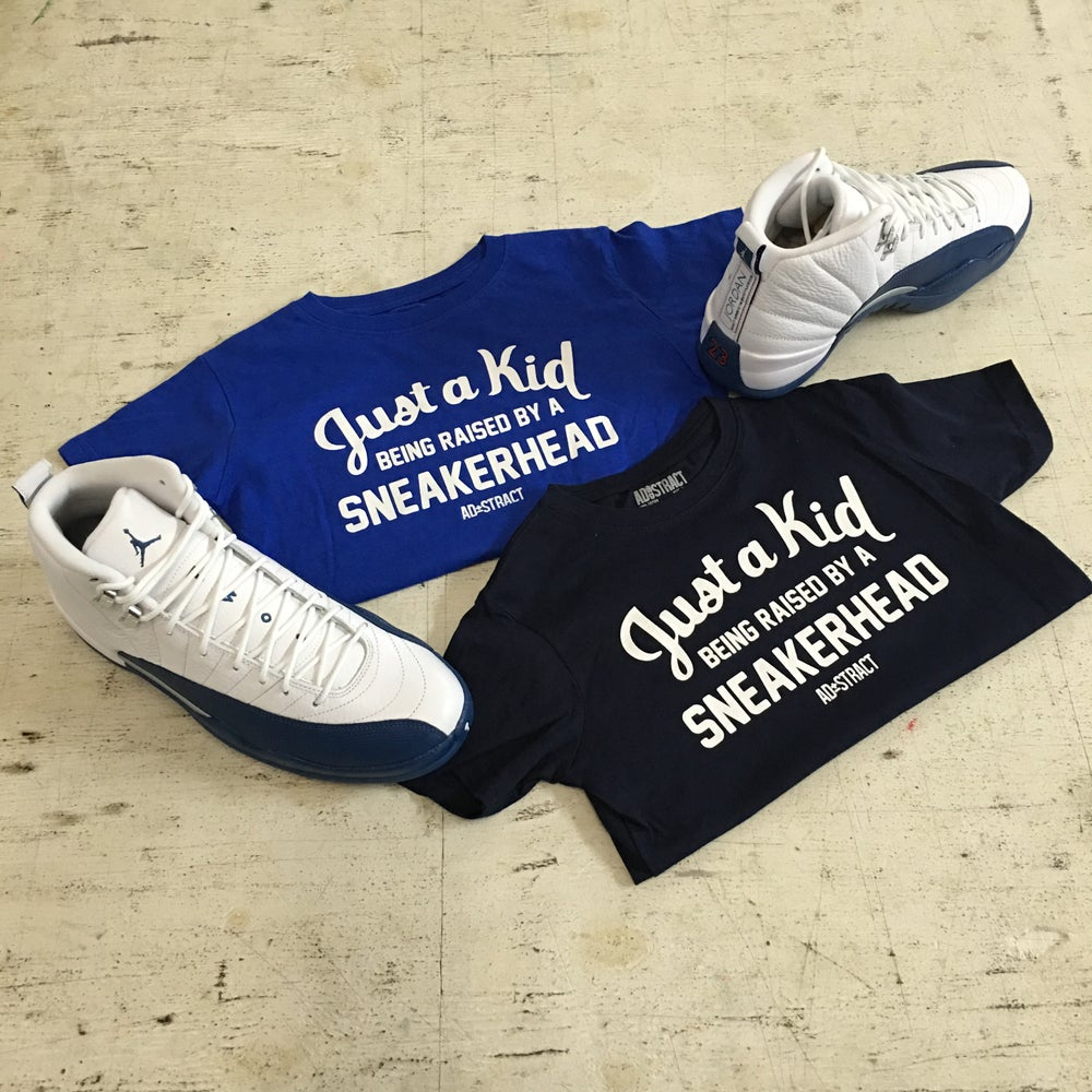 """Image of JUST A KID BEING RAISED BY A SNEAKERHEAD TSHIRT """"BLUE/NAVY"""" (TODDLER)"""