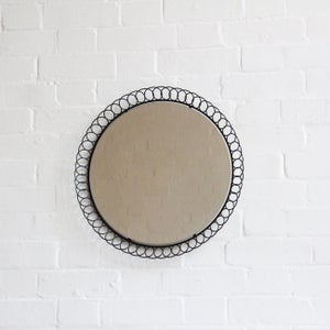 Image of 1960s black mirror with circular frame