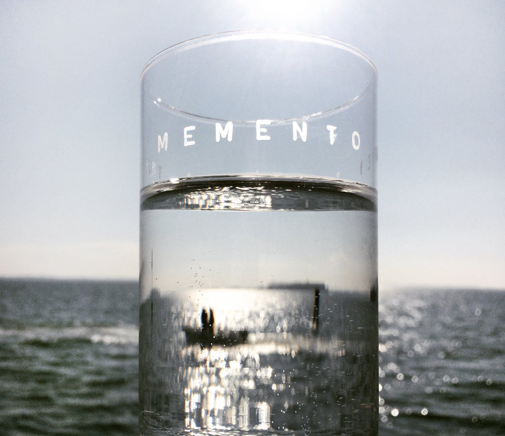 Image of water glass with a Latin inscription