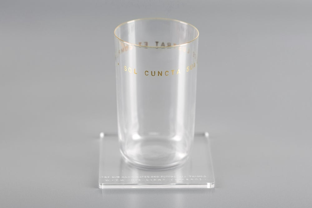 Image of water glass with Latin inscription in gold