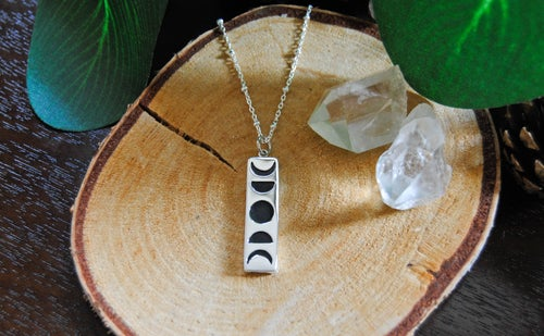 Image of Sterling Silver moon phase set over black wood
