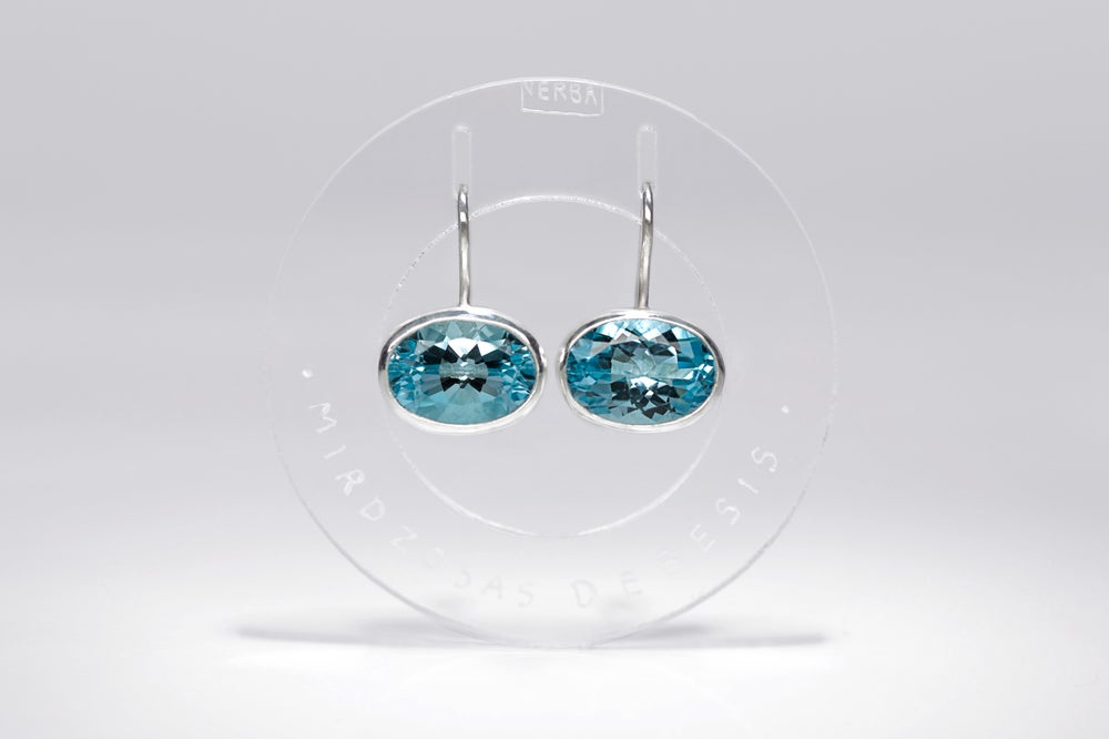 Image of silver earrings with blue topaz FACES CAELI