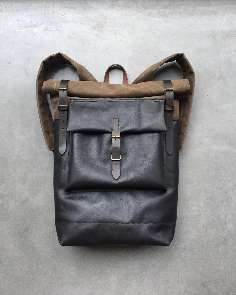 Black leather backpack with waxed canvas roll to close top and leather  front pocket