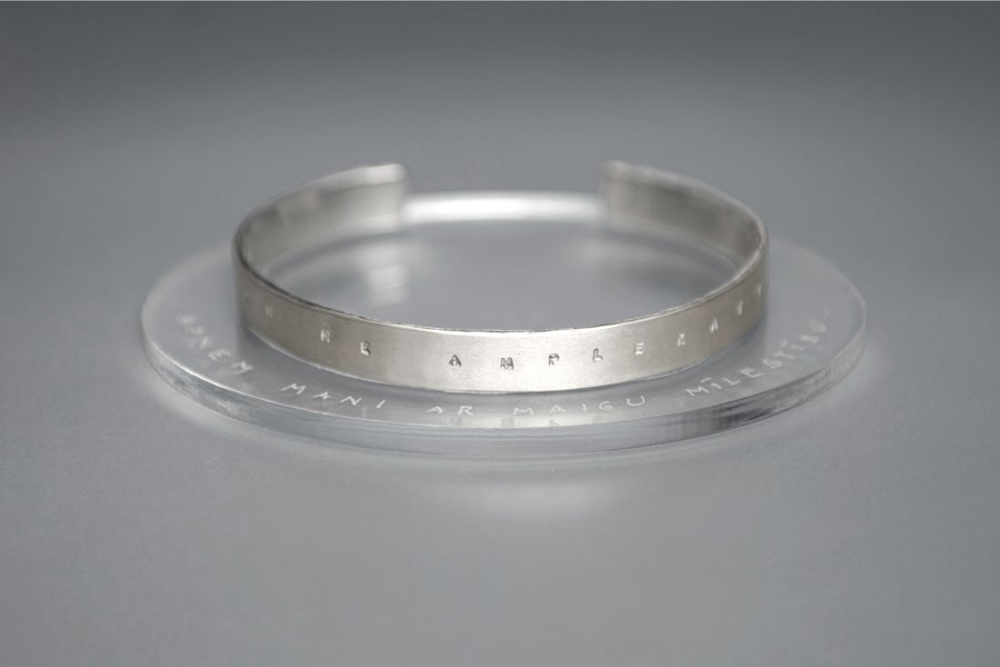 Image of silver bracelet with inscription in Latin