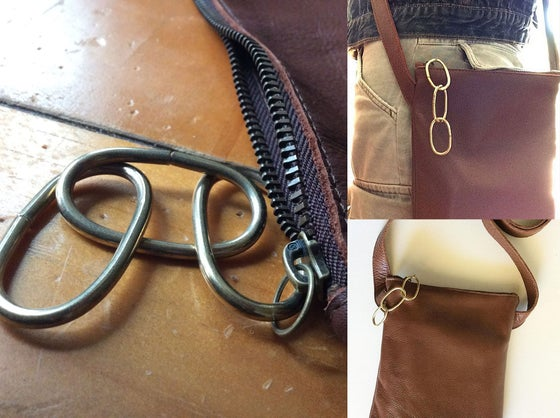 Image of leather cross body with metal chain pull