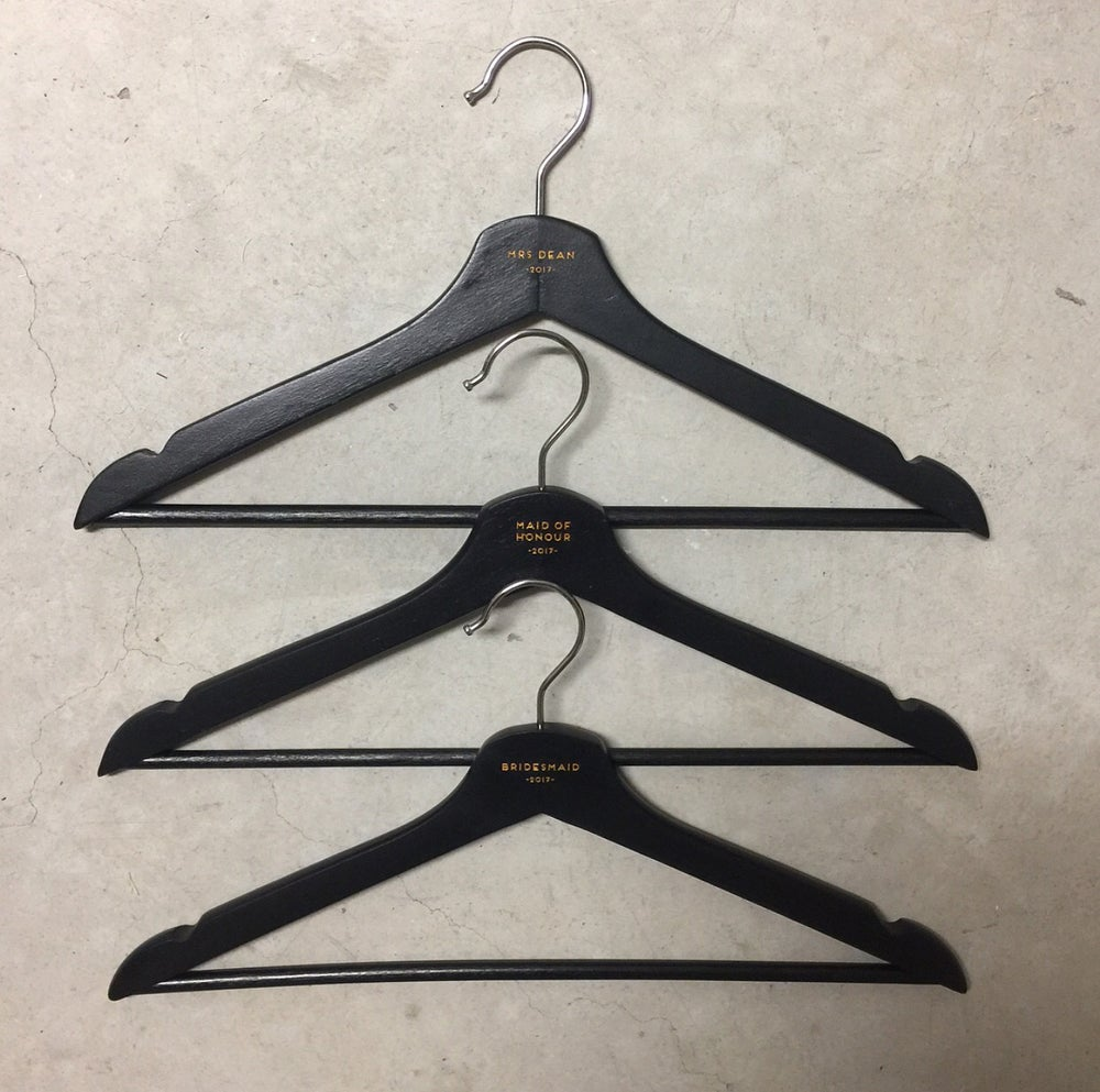 Image of Black wooden hangers with white or gold etching