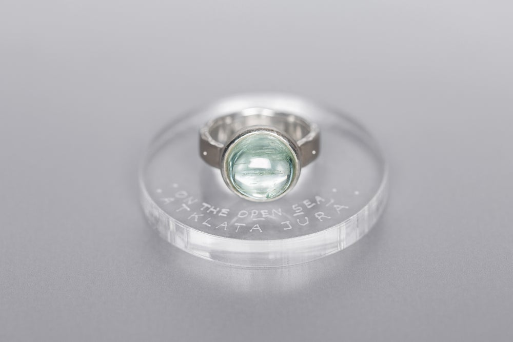 Image of silver ring with aquamarine and inscription in Latin