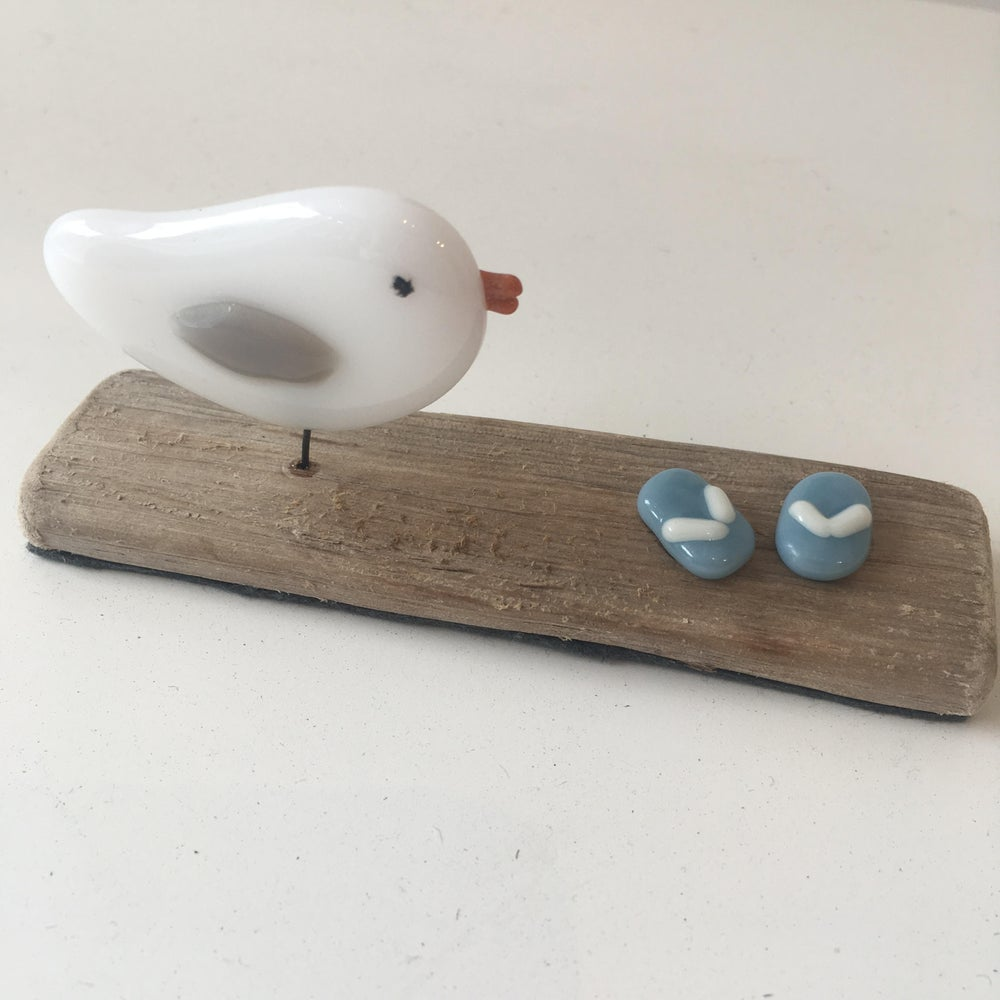 Image of Glass seagull and flip flops on driftwood
