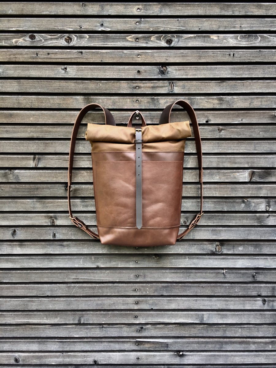 Image of Leather backpack with waxed canvas roll to close top and double outside pocket