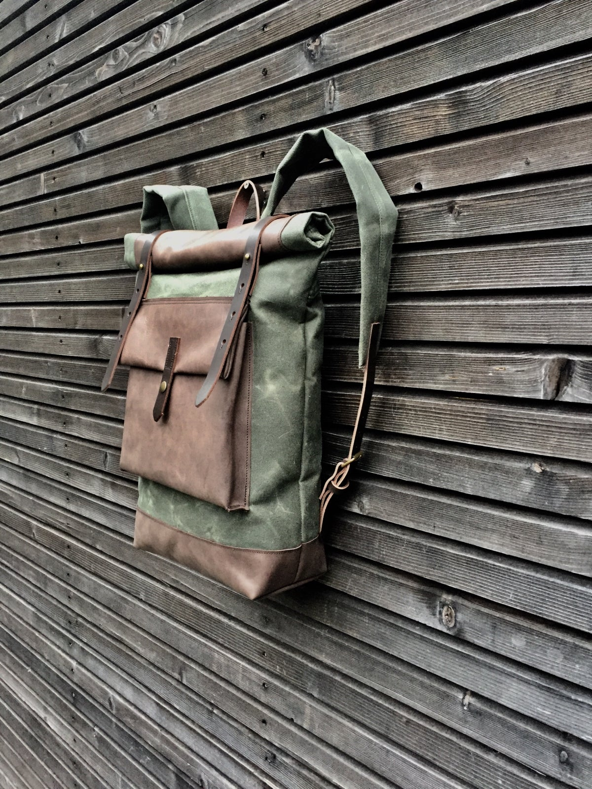 Image of Waxed canvas backpack with roll to close top with leather bottom and outside pocket in dark taupe