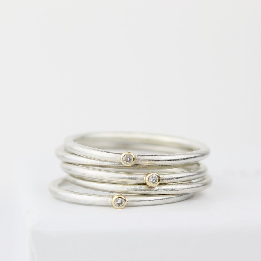 Image of teeny diamond stack (three diamond rings, two plain)
