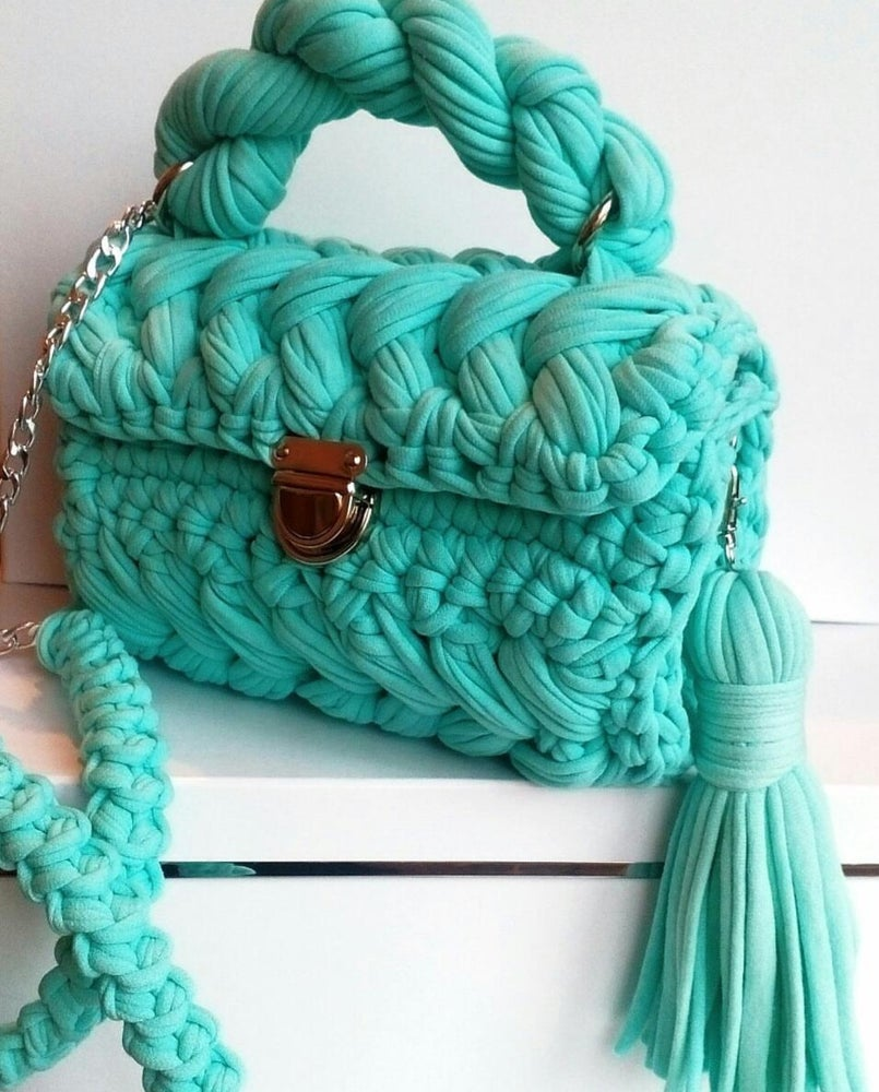 Image of Crochet purses with a handle and chains .