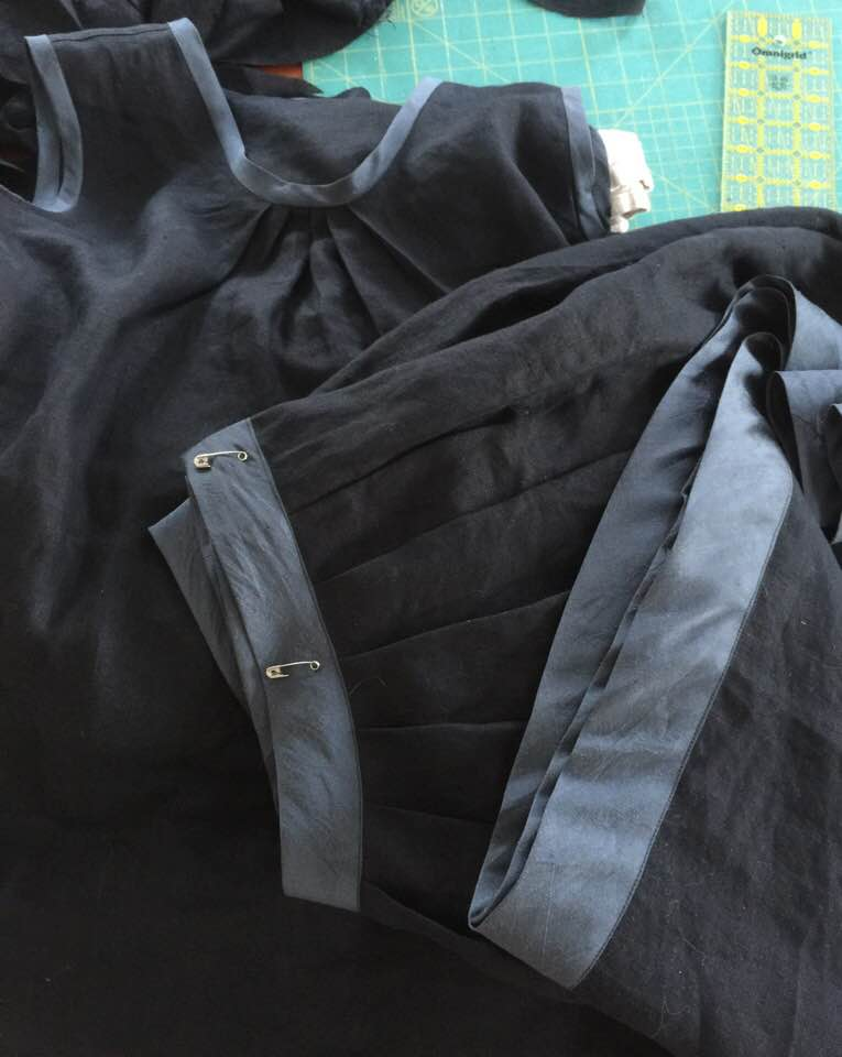 Image of long black linen pleated skirt with silk bands