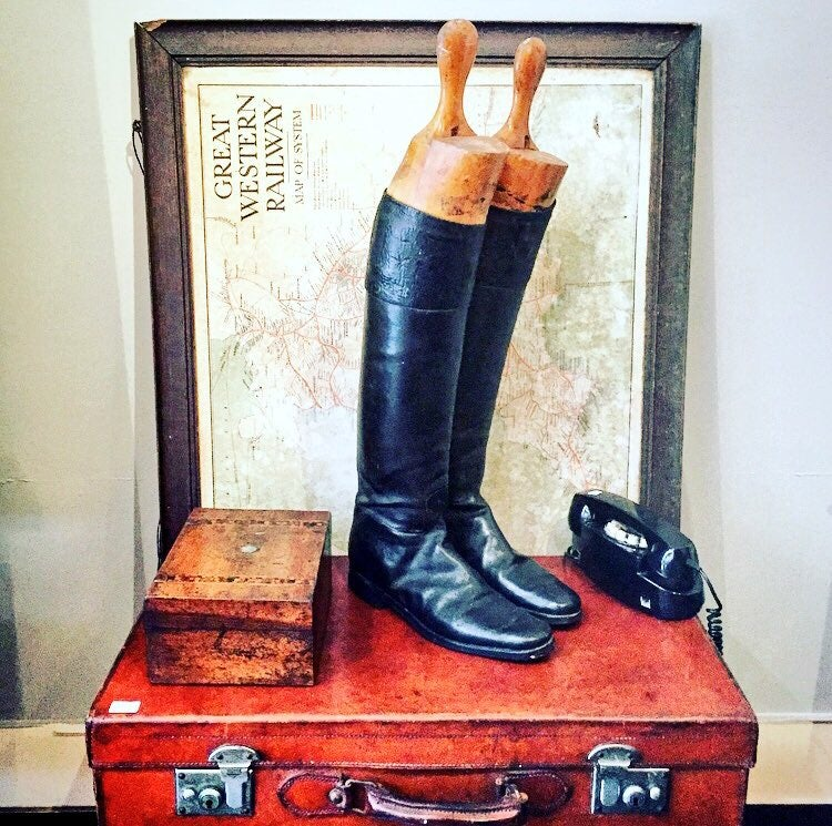 Pair of leather riding boots and antique wooden boot lasts.