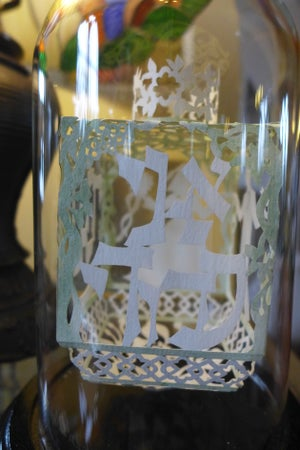 Image of Cut paper wedding dreidel under a glass dome on a wood base