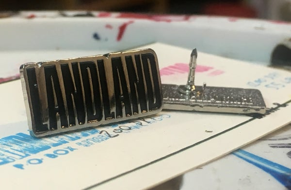 "Image of Landland ""We Have a Logo Now"" Lapel Pin (Silver & Black)"