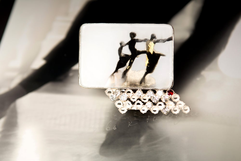 Image of sterling silver brooch with garnet and gold leaf on ballet photography under glass