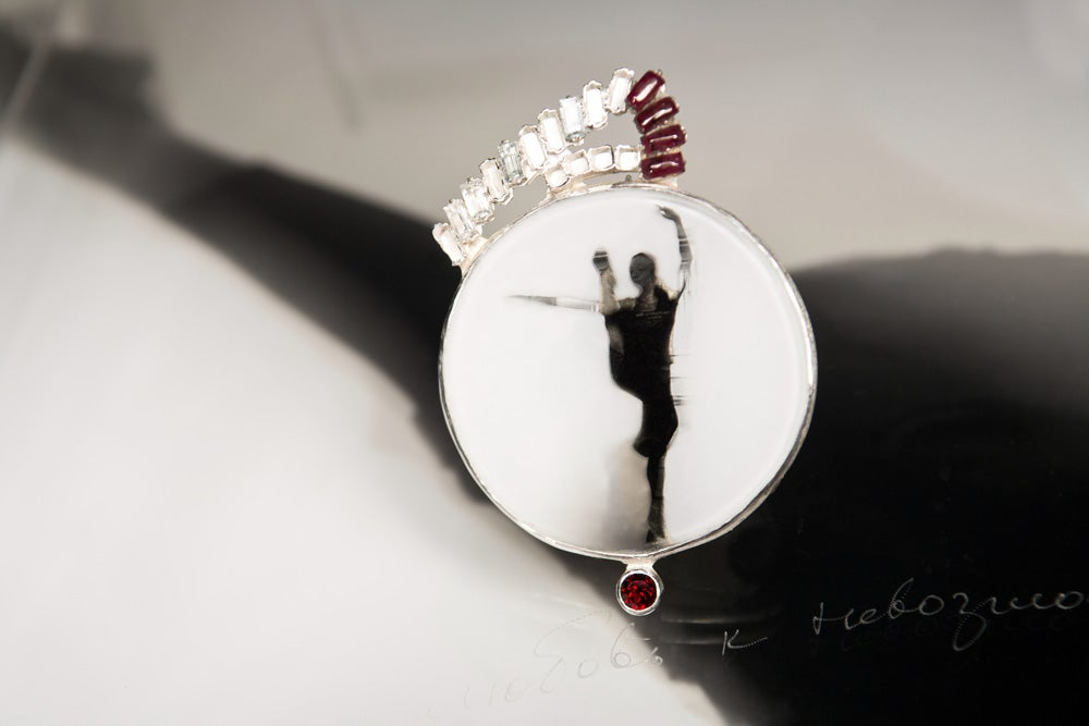Image of round sterling silver brooch with topaz, garnets and ballet photography under glass