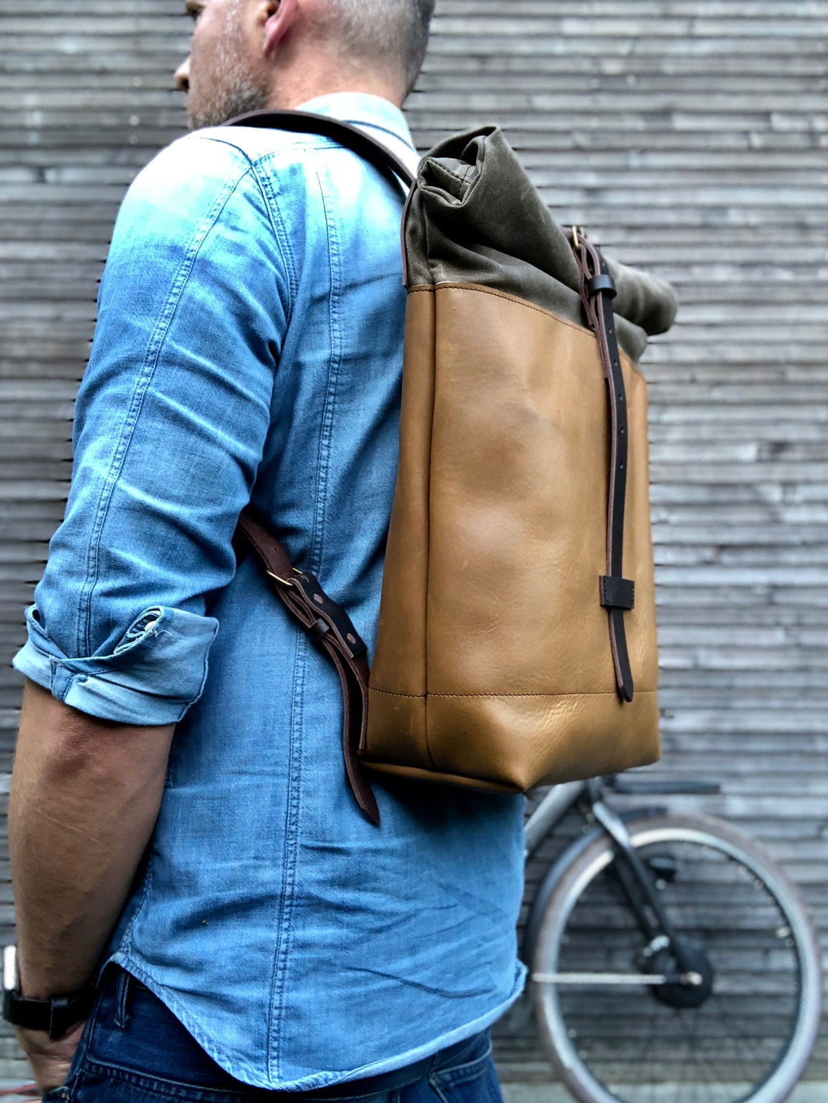 Image of Leather backpack with waxed canvas roll to close top and vegetable tanned shoulder straps