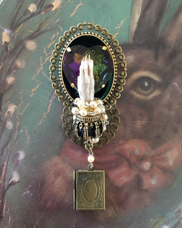 Image of Taxidermy brooch featuring one rat paw and greenish purple rhinestone.