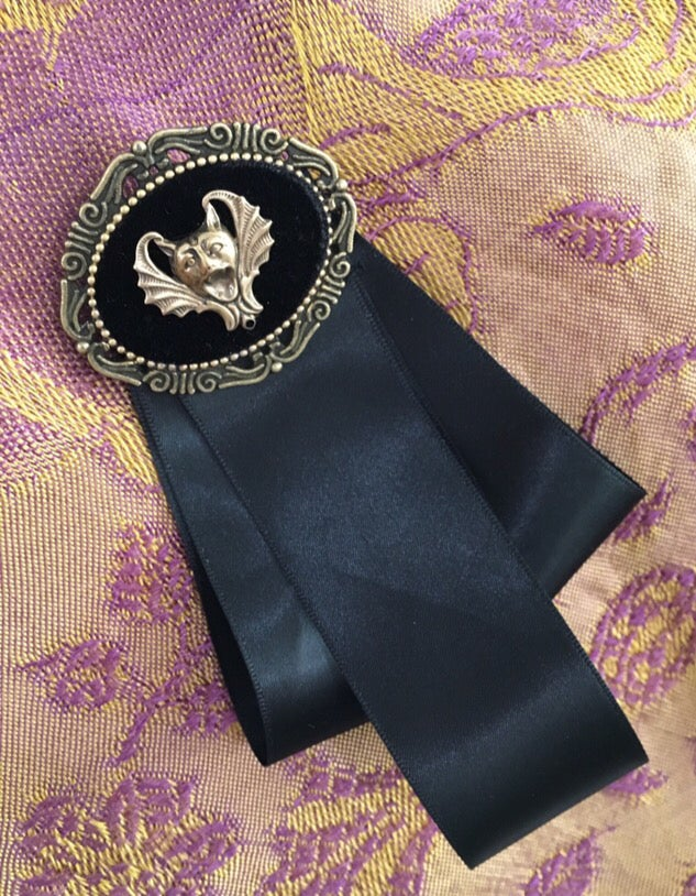 Image of Screaming bat face brooch with black ribbons