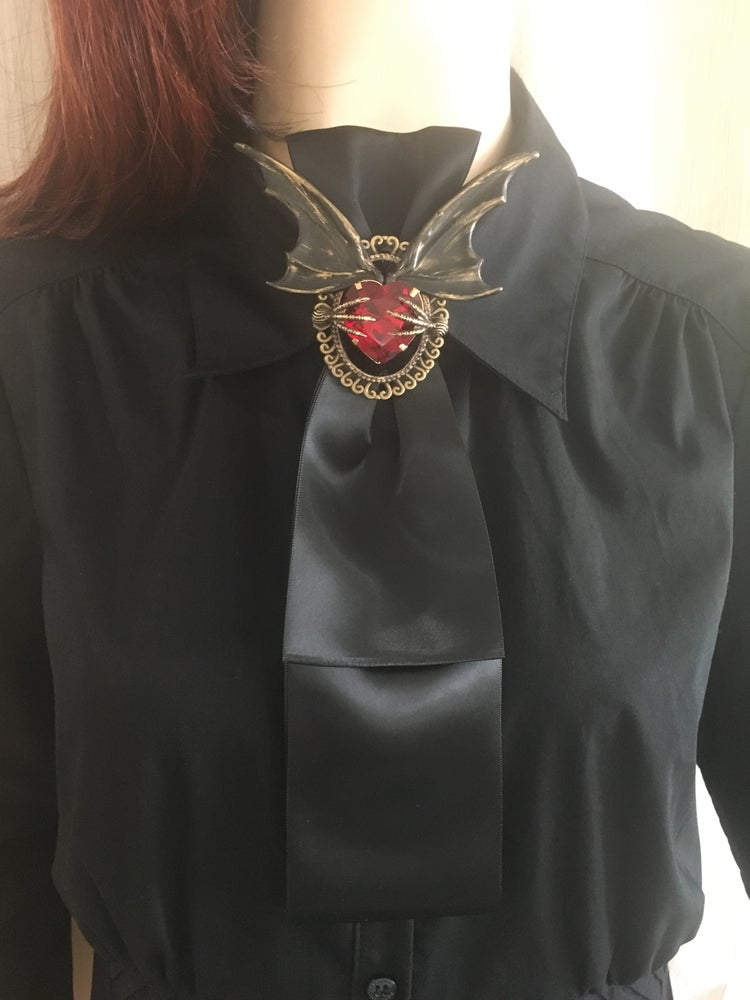 Image of Goth black ribbon tie featuring bat wings and a red rhinestone with raven claws