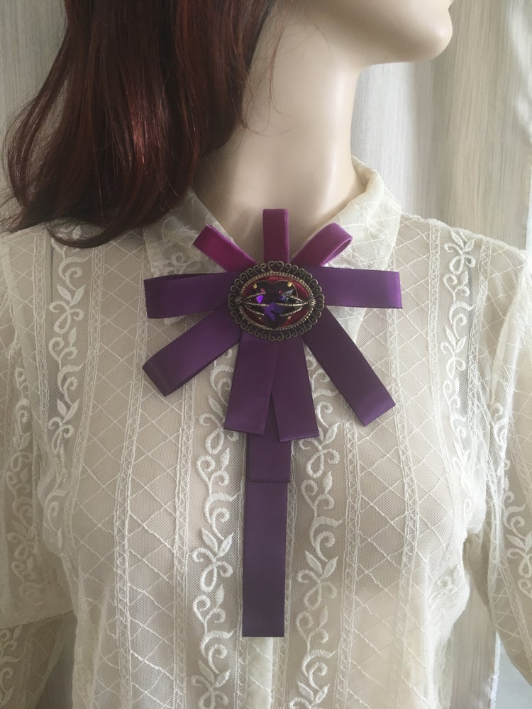 Image of Purple ribbon brooch featuring purple rhinestone and raven claws