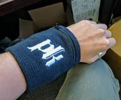 Image of PK logo wrist cuff with zippered pocket