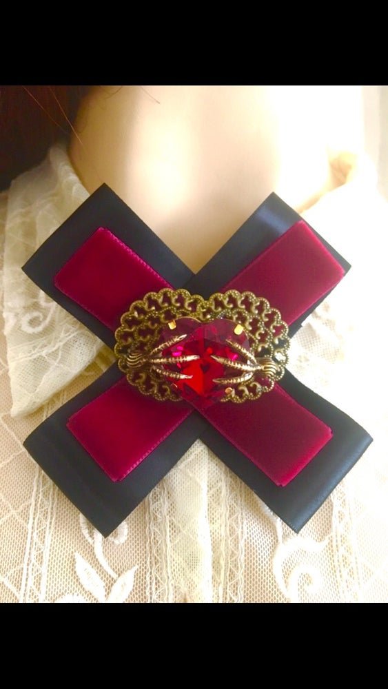 Image of Raven claw clutching red rhinestone heart brooch