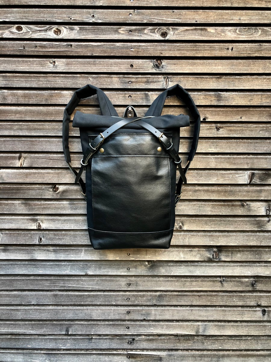 Image of Black backpack medium size rucksack in waxed canvas, with leather front pocket and bottom