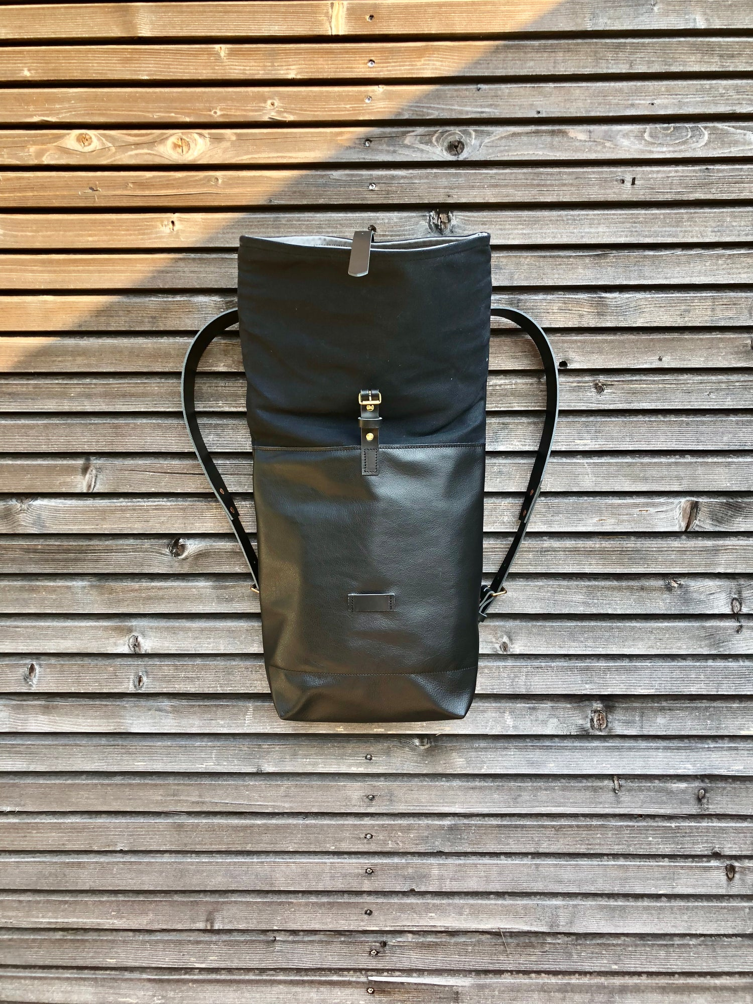 Image of Black leather backpack with waxed canvas roll to close top