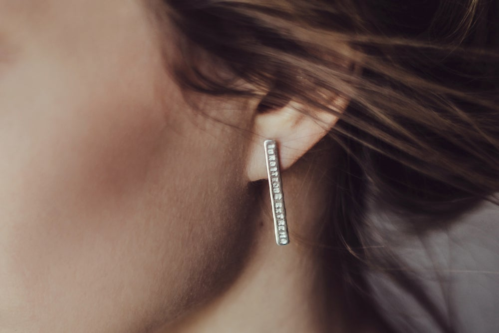 Image of long plain silver earrings with inscription in Latin