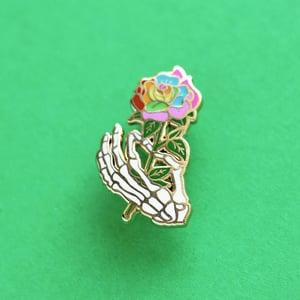 Image of Skeleton hand holding a rainbow rose, enamel pin - bones - skeleton pin - anatomy - lapel pin badge