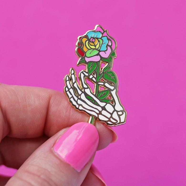 Image of Skeleton hand holding a rainbow rose, enamel pin - bones - skeleton pin - anatomy - lapel pin badge