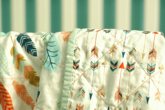 Image of Feathers & Arrows Wholecloth Cotton Baby Quilt