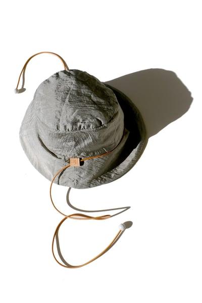 Image of reversible silver nylon bucket hat