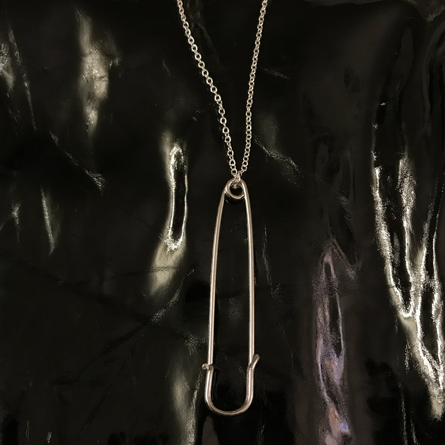 Image of safety pin pendant on loop chain