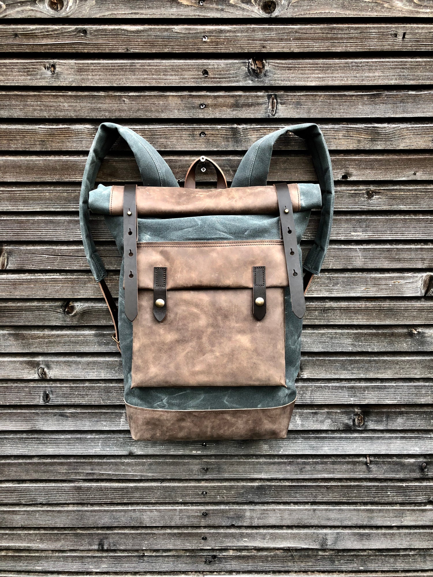 Image of Waxed canvas backpack with roll up top and hand waxed leather bottom and outside pocket