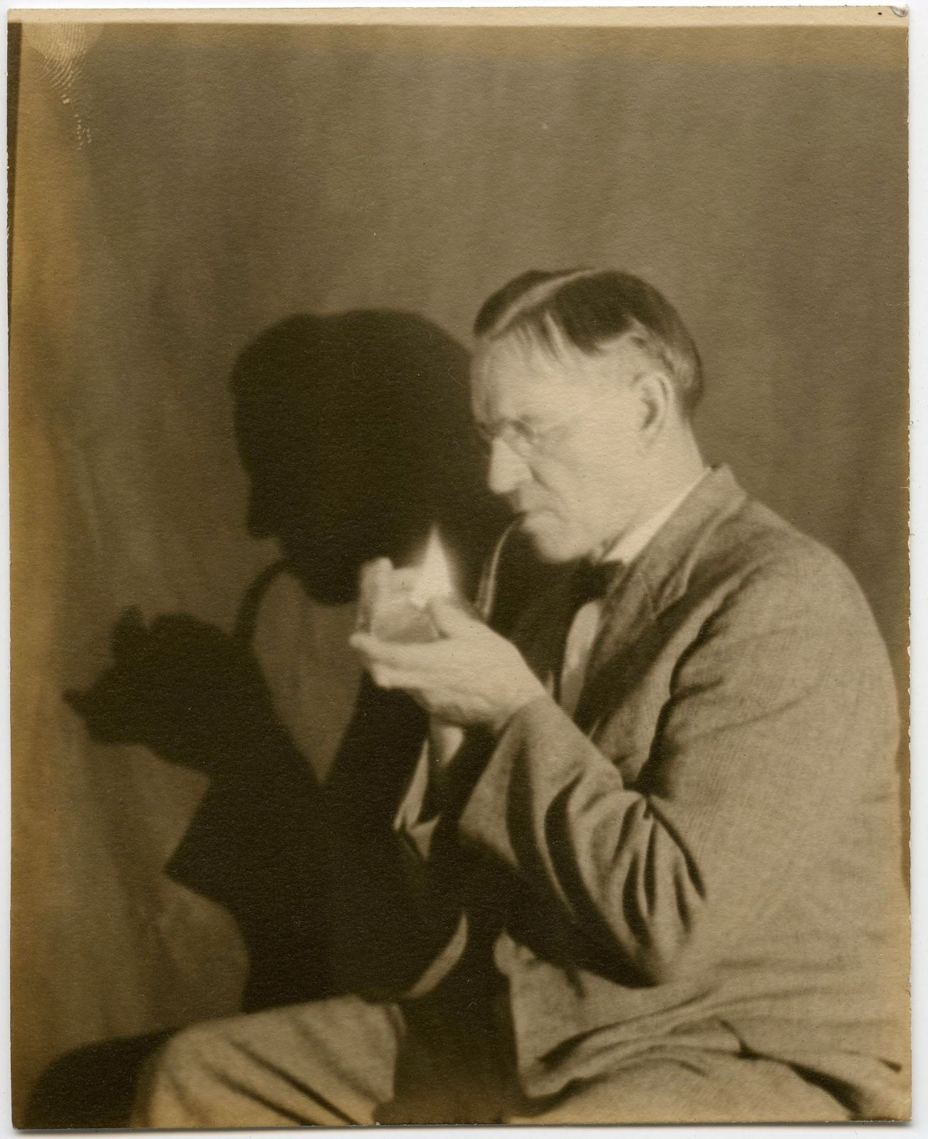 Image of Anonymous: man lighting his pipe with fascinating shadow, ca. 1935