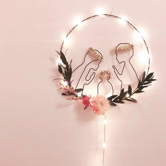 Image of Crèche lumineuse en fil de fer brut et fleurs